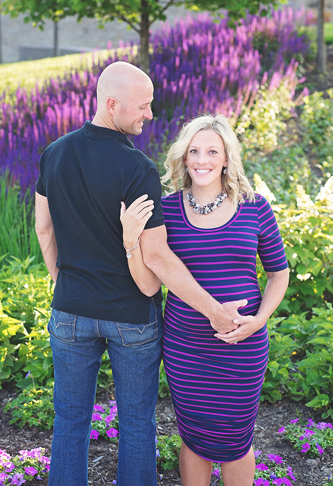 maternity session in cincinnati ohio mom and dad happy in front of pretty purple flowers
