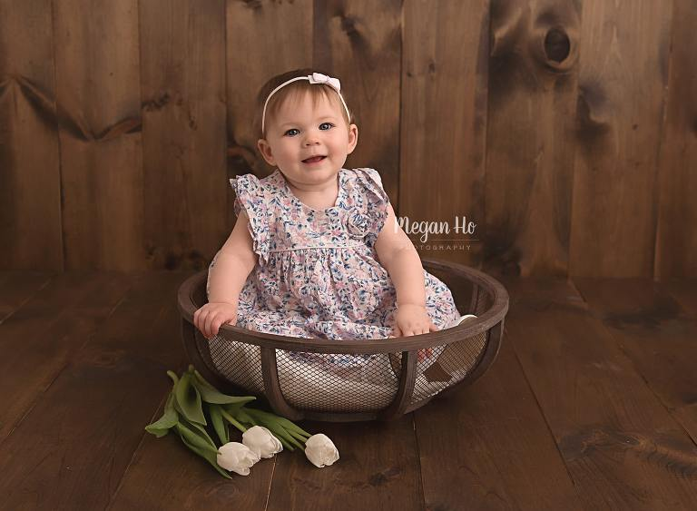 one-year-girl-sitting-in-wood-bowl-with-tulips-new-hampshire-session