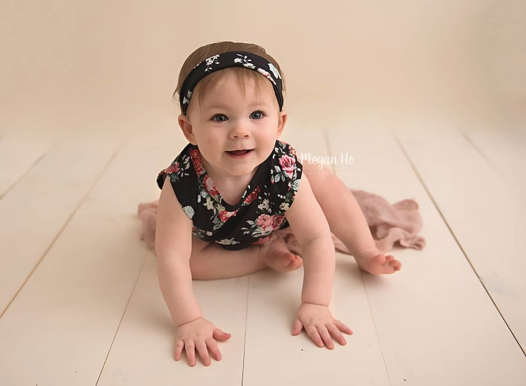 smiling-one-year-old-girl-in-floral-romper-bedford-nh-studio