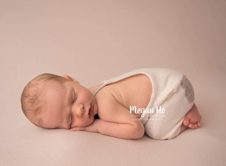 sleeping baby boy on tan fabric in tushie up pose in new hampshire