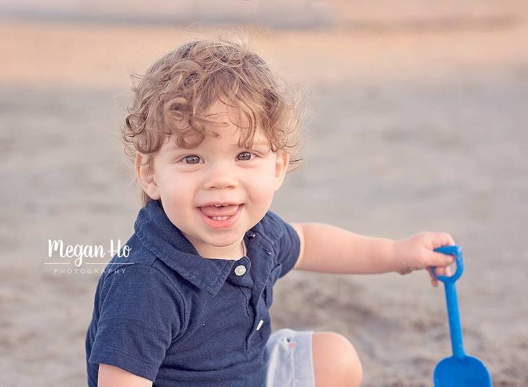 one year boy with brown curls smiling on nh beach with blue shovel