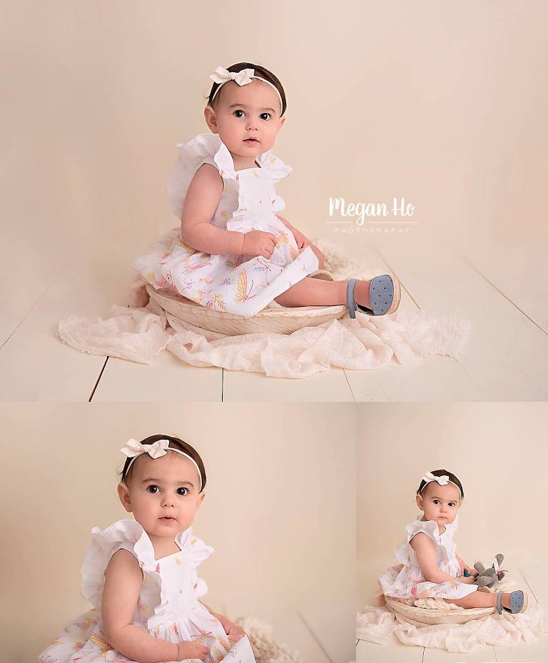 pretty baby girl sitting in a white bowl in dress in one year milestone session nh