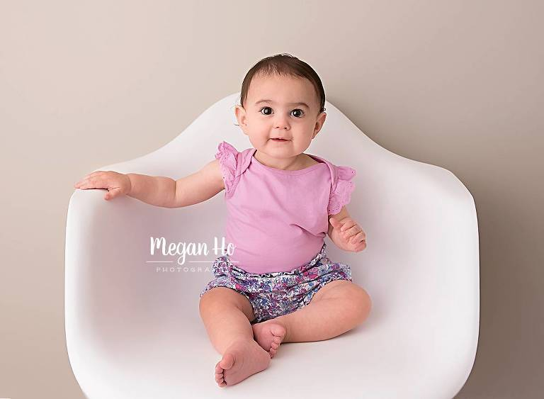 happy smiling toddler girl in pink and flower shorts in chair during studio session in southern nh