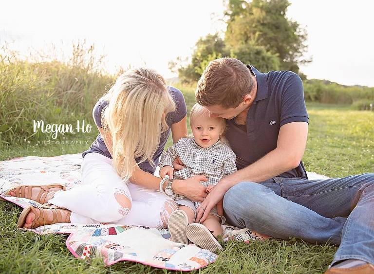 nh family sitting on quilt in the grass tickling one year boy