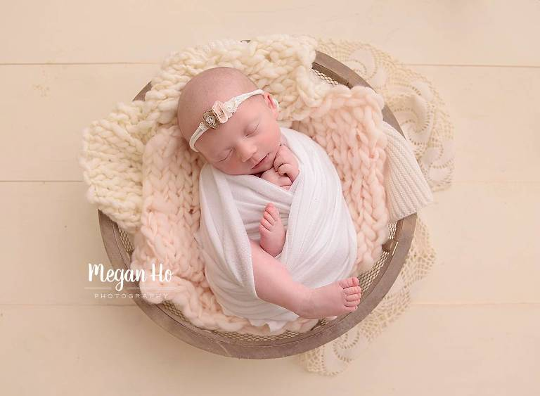 wrapped little baby girl in white in little bowl on wood floor