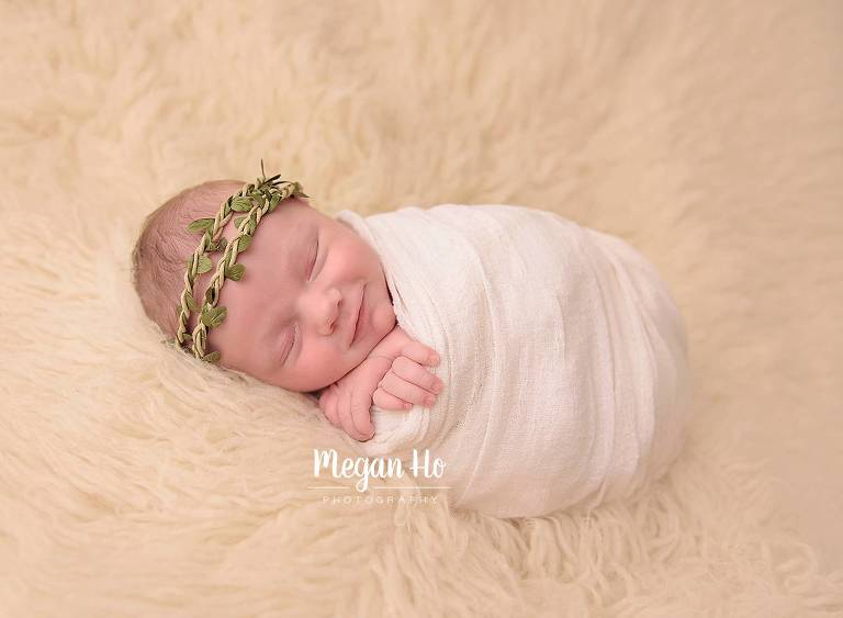 smiling little girl wrapped in white with green halo sleeping during studio session in new hampshire