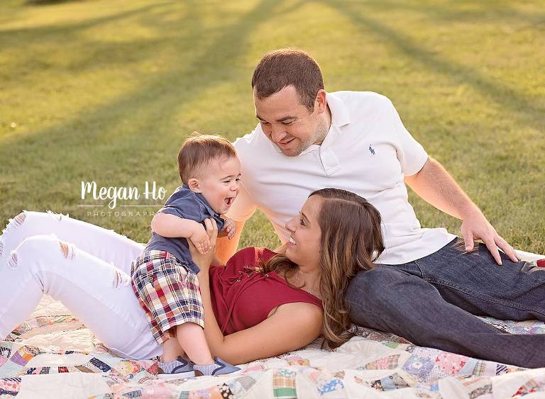 southern nh family session on summer night adorable family of three laughing and sitting on large quilt