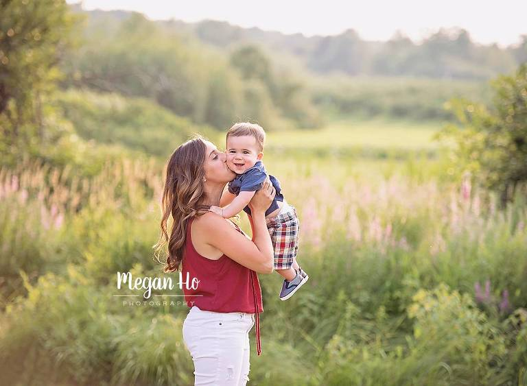 beautiful mama kissing baby boy on cheek in beautiful Londonderry nh family session on summer night