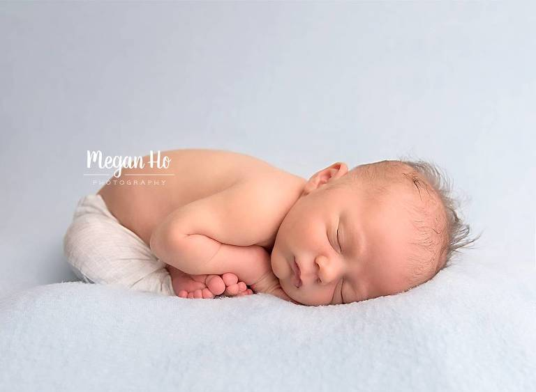 adorable new hampshire baby boy sleeping on blue blanket with toes showing