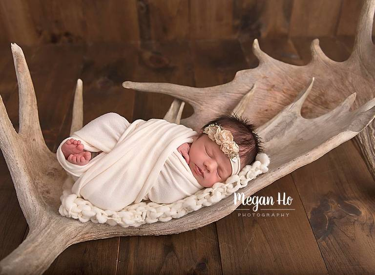 beautiful baby wrapped girl sleeping on moose antlers bedford new hampshire