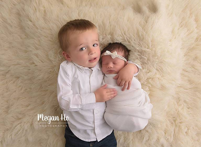 big brother snuggling with baby sister on white fluffy rug southern nh newborn session