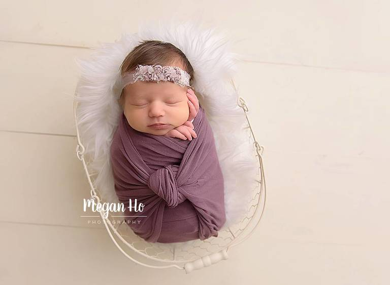 Swaddled baby in purple wrap snuggled in basket nh studio