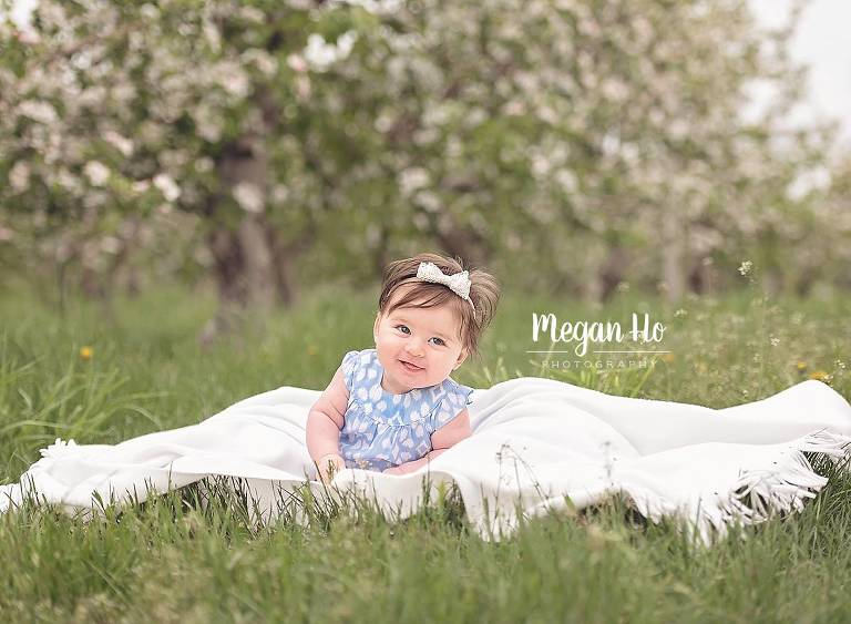 baby girl sitting on white blanket in nh apple orchard