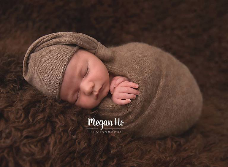cute sleeping boy wrapped in boy on brown fluffy rug in nh session
