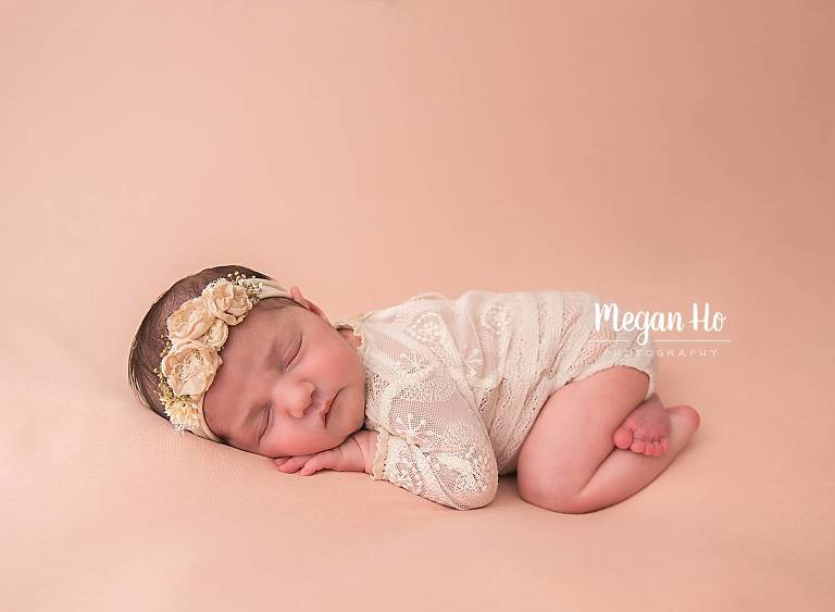 sweet newborn girl in lace outfit on peach backdrop in nh studio