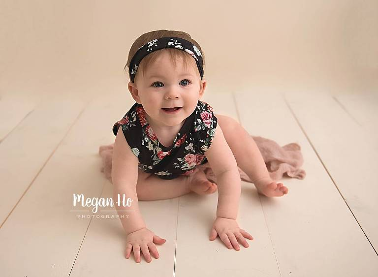 smiling one year old girl in floral romper bedford nh studio
