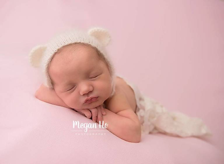 newborn baby girl on pink blanket with white bear bonnet