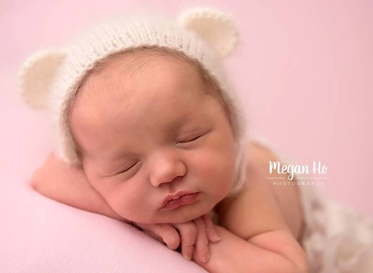 baby girl on pink backdrop with white bear hat on in bedford nh studio session