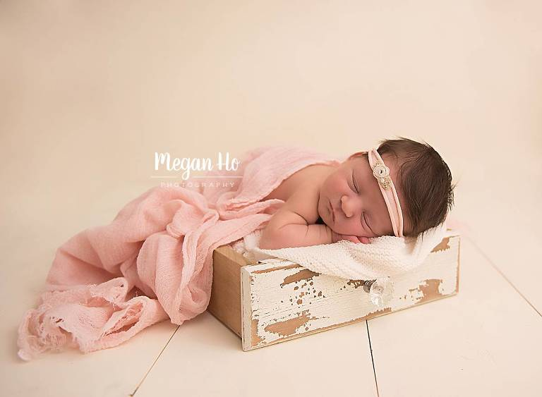 nh newborn girl sleeping in antique wood drawer on white wood