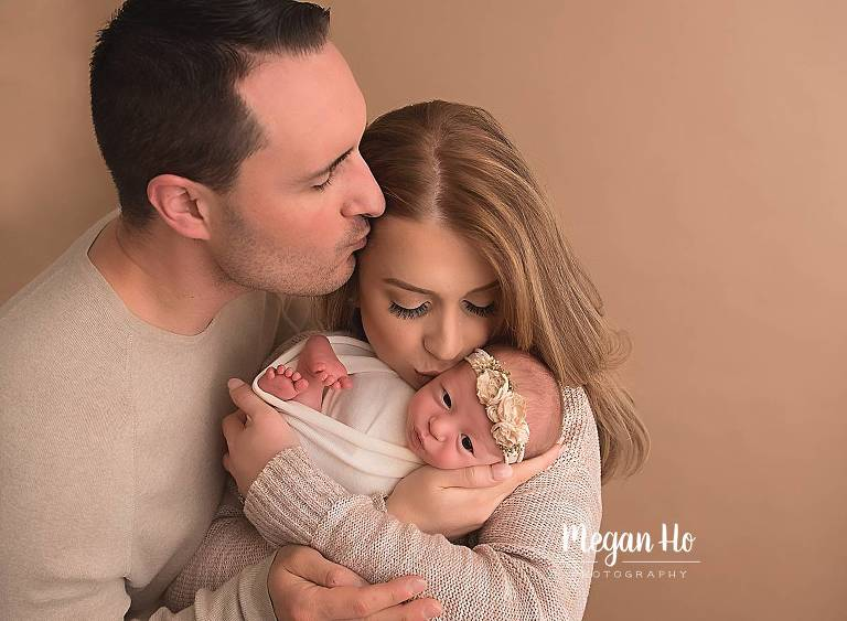 new parents kissing their brand new baby girl bedford nh