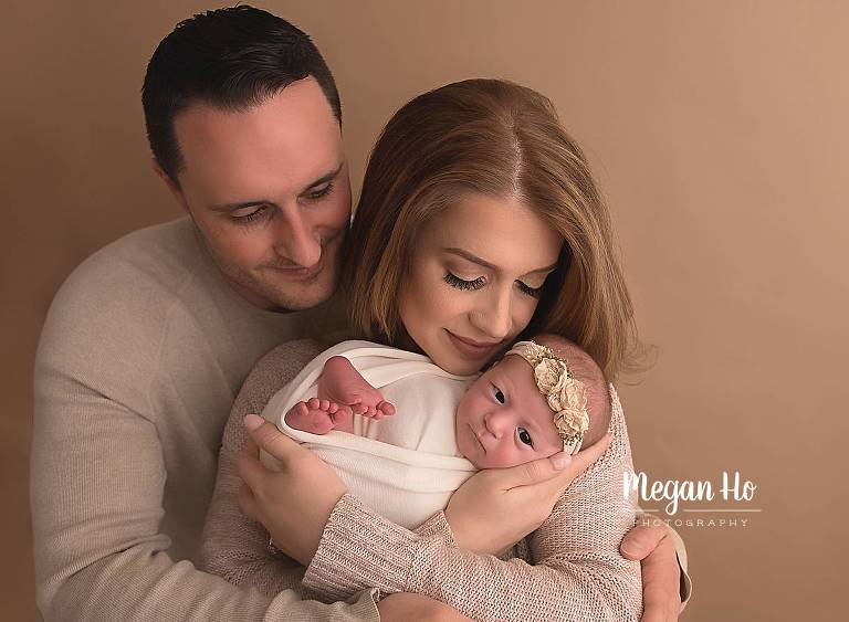 mom and dad snuggling brand new baby girl nh studio session