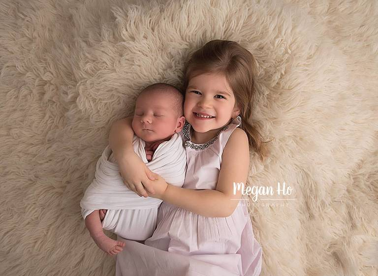 newborn boy snuggling with big sister on white fluffy rug southern nh studio