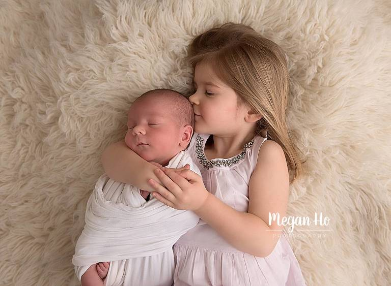 big sister holding and kidding wrapped newborn baby brother in nh newborn session