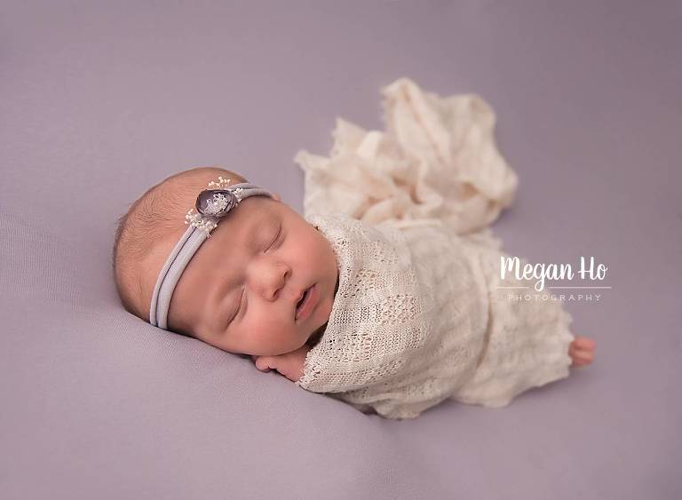 newborn girl wrapped in lace on purple sleeping sweetly in newborn session