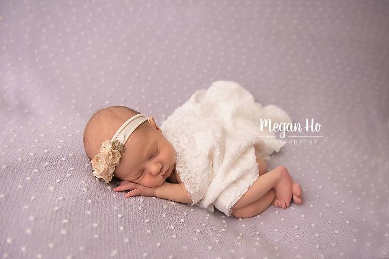 sleeping newborn girl on purple covered in lace in nh studio