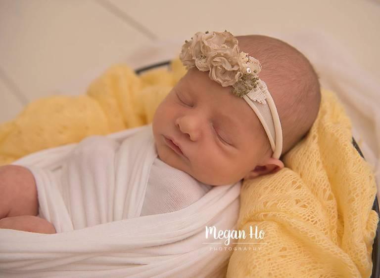 newborn baby girl swaddled in bowl on yellow blanket