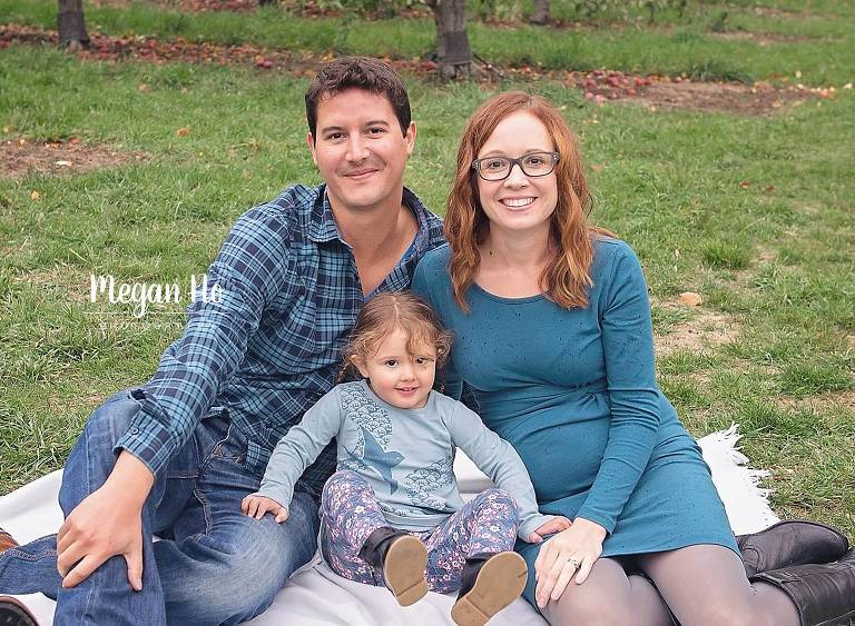 family of soon to be four in blue sitting on blanket in fall session