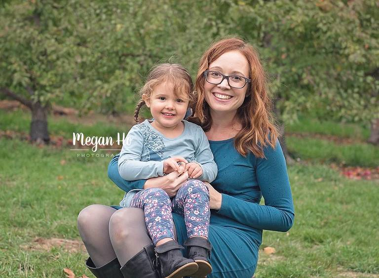 toddler girl in blue sitting on moms lap in nh apple orchard