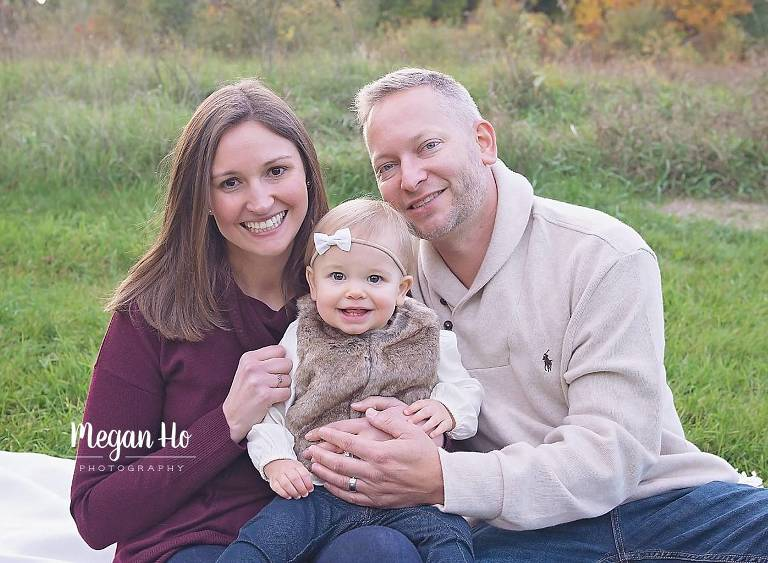 nh family session beautiful family of three sitting on a blanket in fall