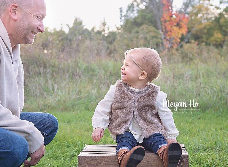 little girl sitting on a crate smiling at dad in nh family session