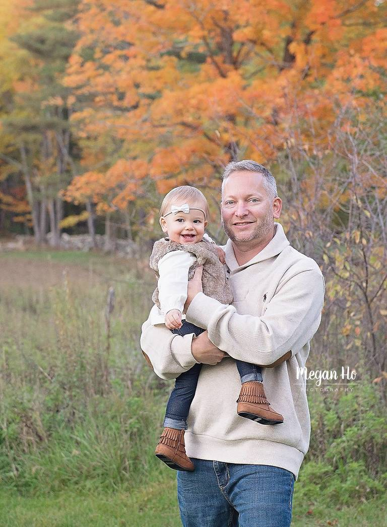 dad holding one year old girl in nh fall session in front of orange leaves tree
