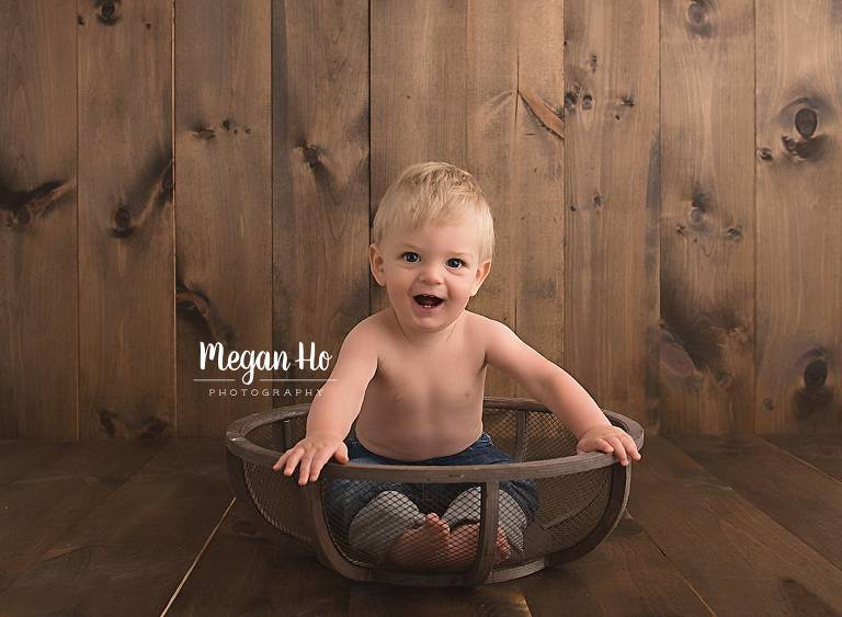 happy one year old boy in jeans sitting in wooden bowl