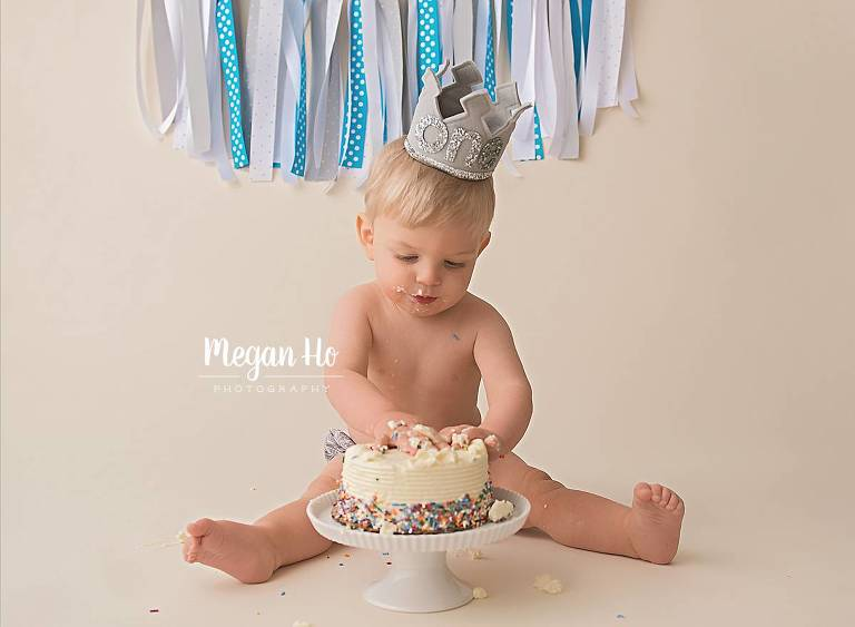 one year boy sitting by cake with grey one crown and blue banner