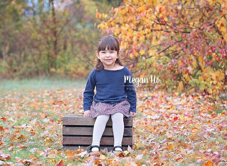 little girl sitting on crate with fall leaves all around