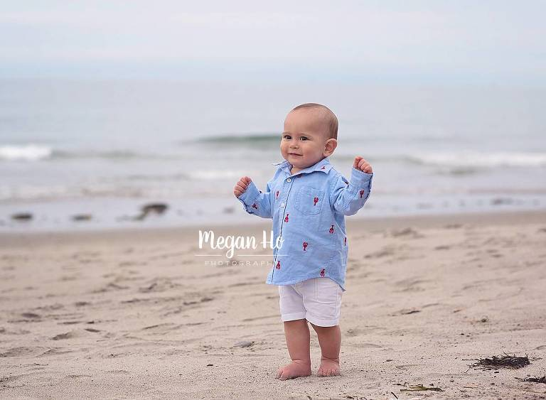 happy boy in lobster shirt walking along beach at one year photo session