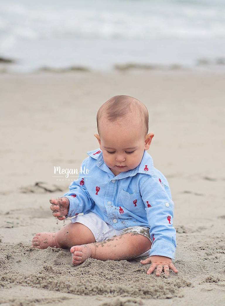 nh one year old sitting covered in sand on beach