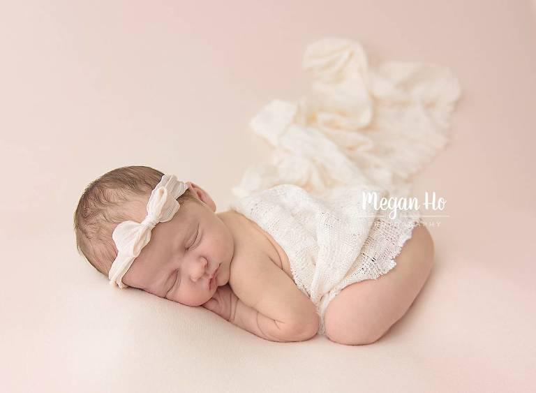 sleeping baby girl on blush blanket covered in lace