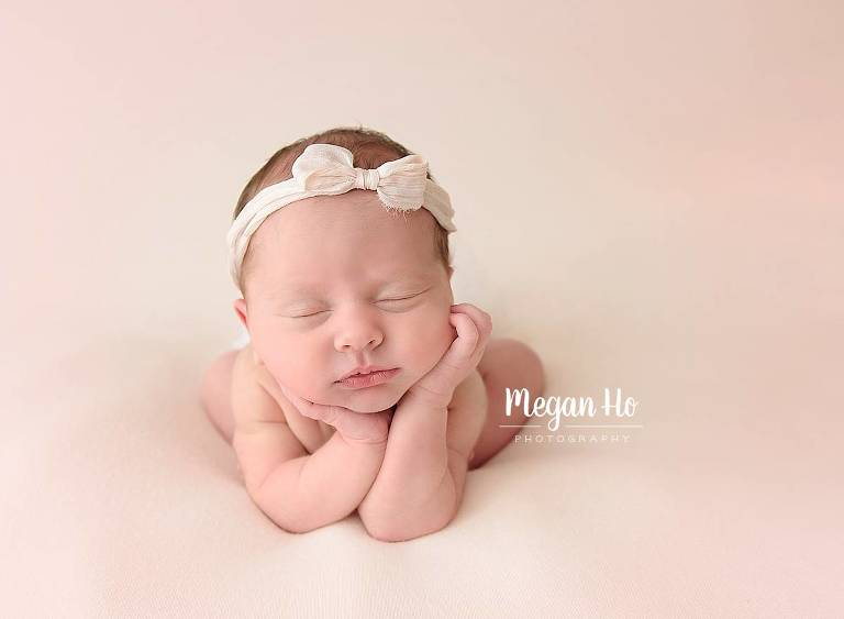 nh newborn baby girl sleeping in froggy pose with pink bow