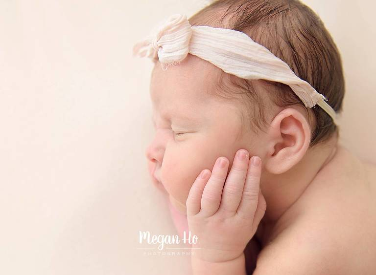 sleeping newborn girl with tiny fingers on face