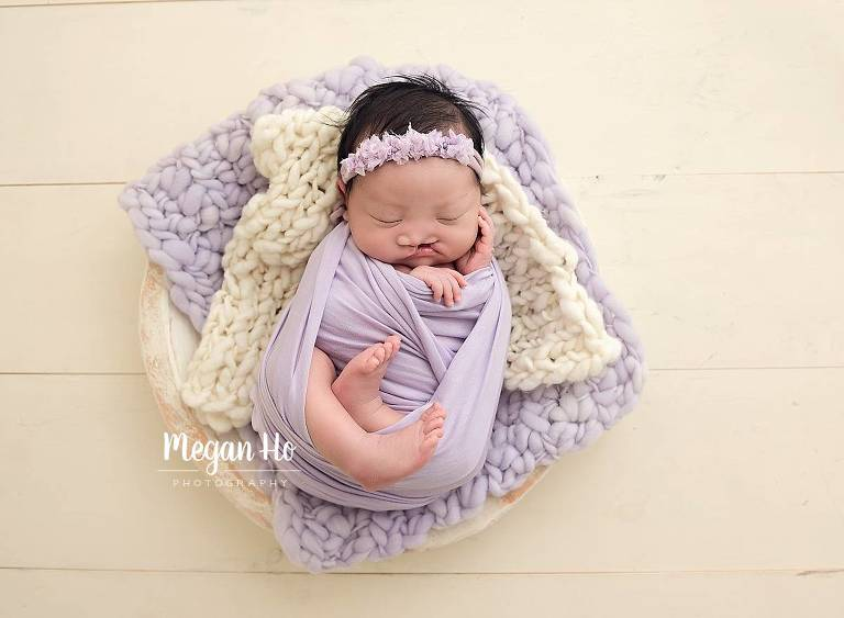 sleeping baby girl with cleft palate wrapped in purple on two bump blankets in southern nh