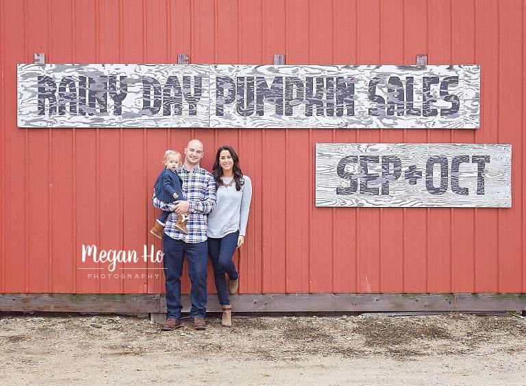 family standing in front of red barn in southern nh outdoor session