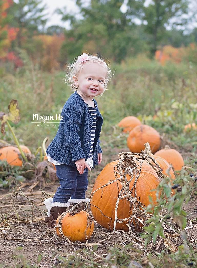 smiling girl standing in front of big pumpkins in Londonderry nh