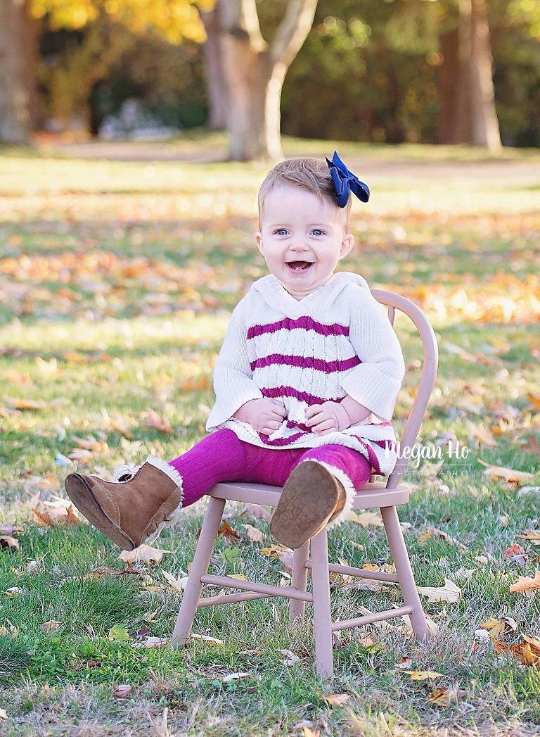 little girl sitting on chair in pink and white sweater in fall park