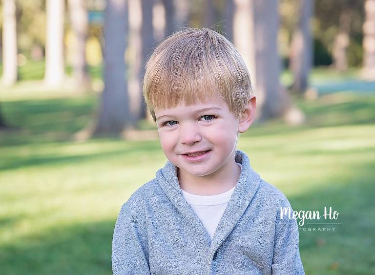 three year boy with grey sweater sitting and smiling in park