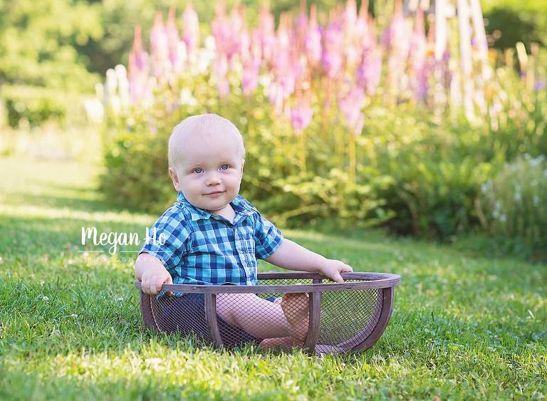 one year boy sitting in a mesh bowl in front of purple flowers