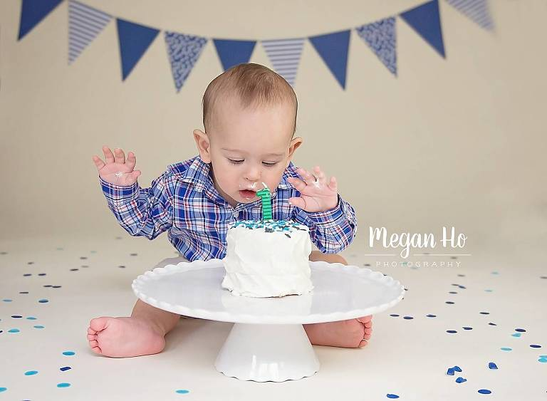 blue and white cake smash little boy going to stick face in cake